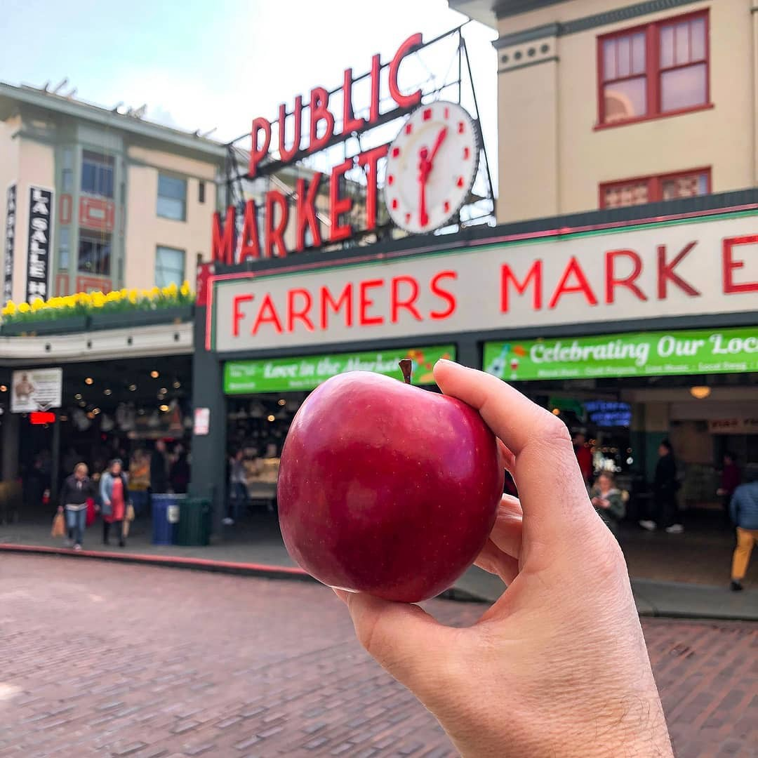 A Cosmic Crisp apple in front of a public market.