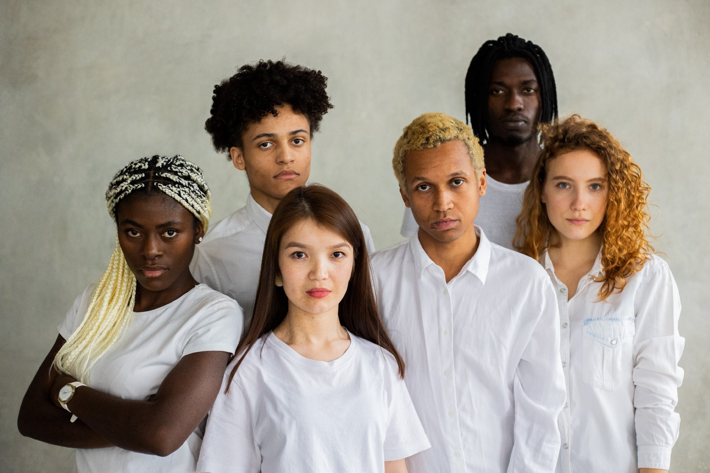 A group of diverse young people stand together, looking at the camera.