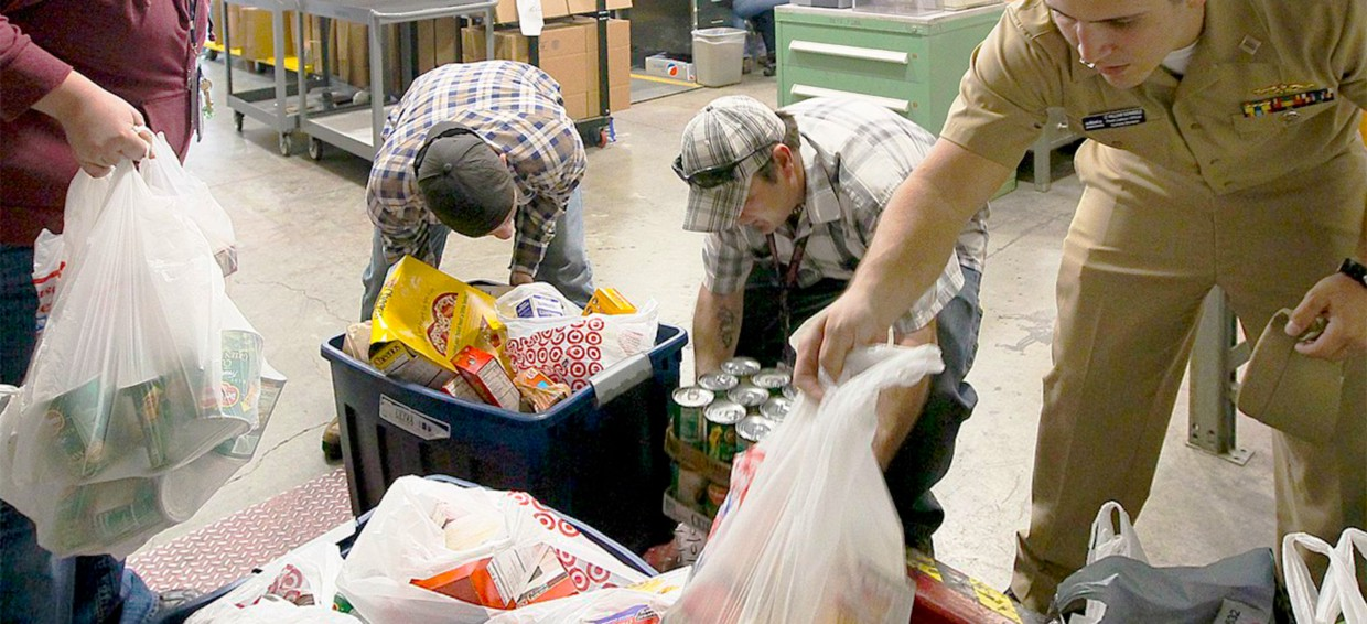 Volunteers are sorting donations of food at a food bank.