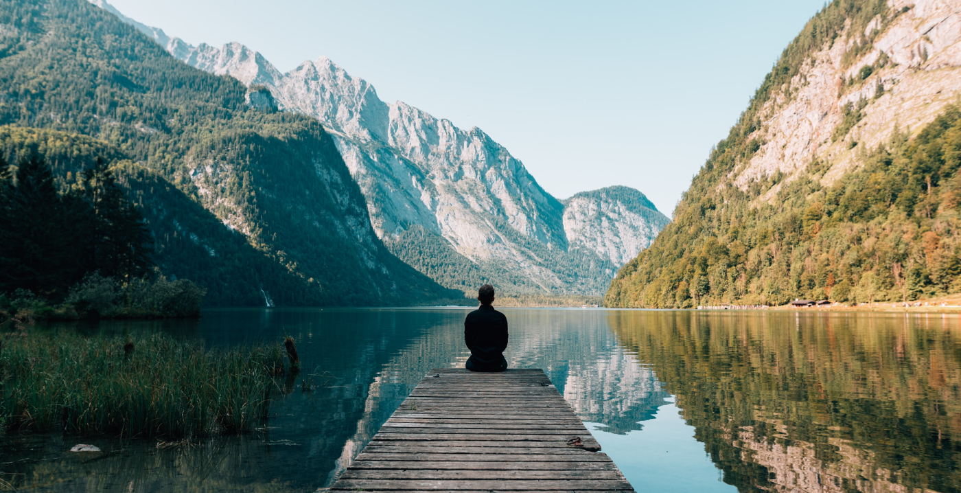 a person sitting on a wooden bridge at a crystal clear lake surrounded by mountains, meditating