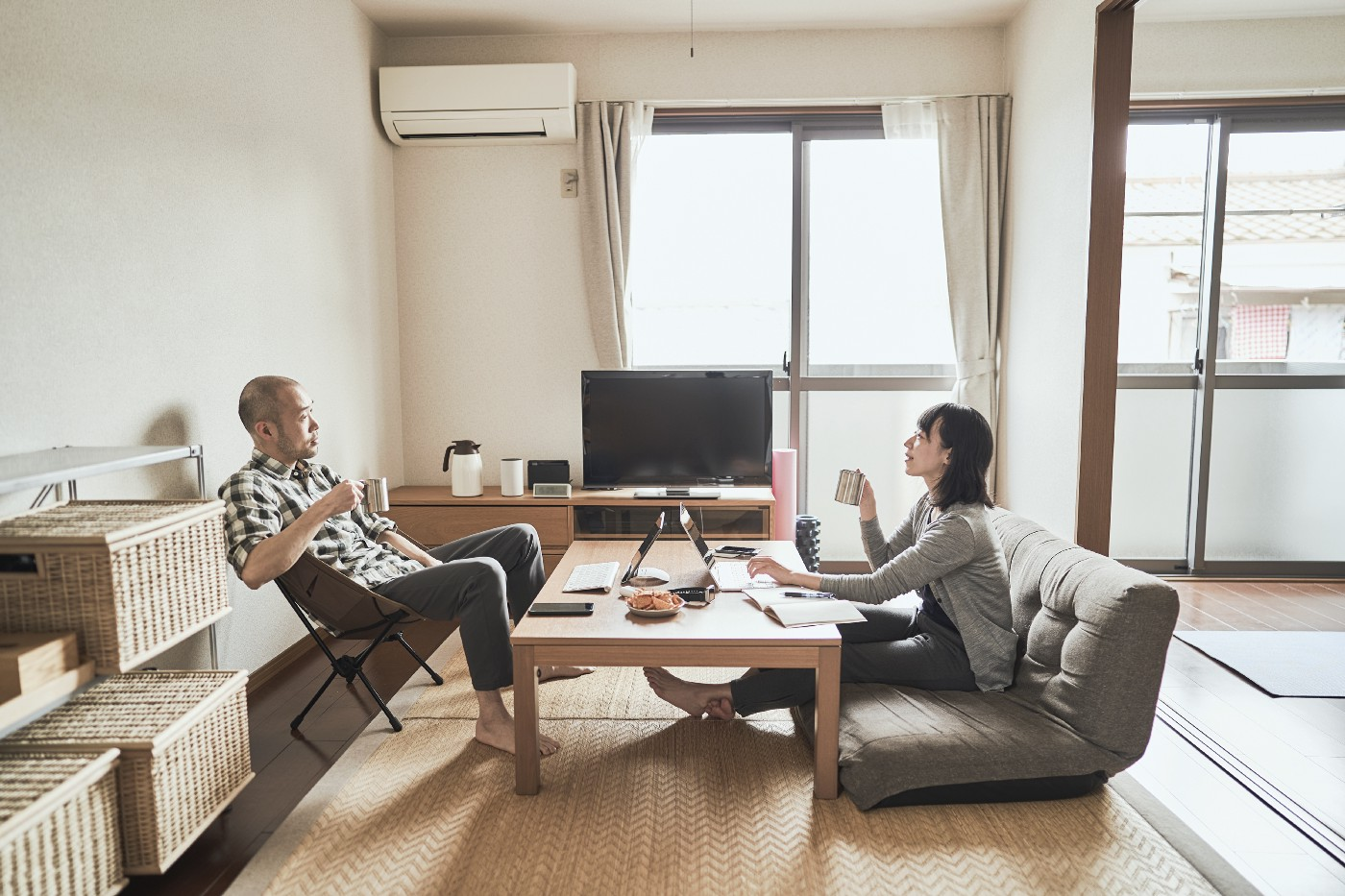 A couple sits on opposite sides of a coffee table, working on their laptops together at home.