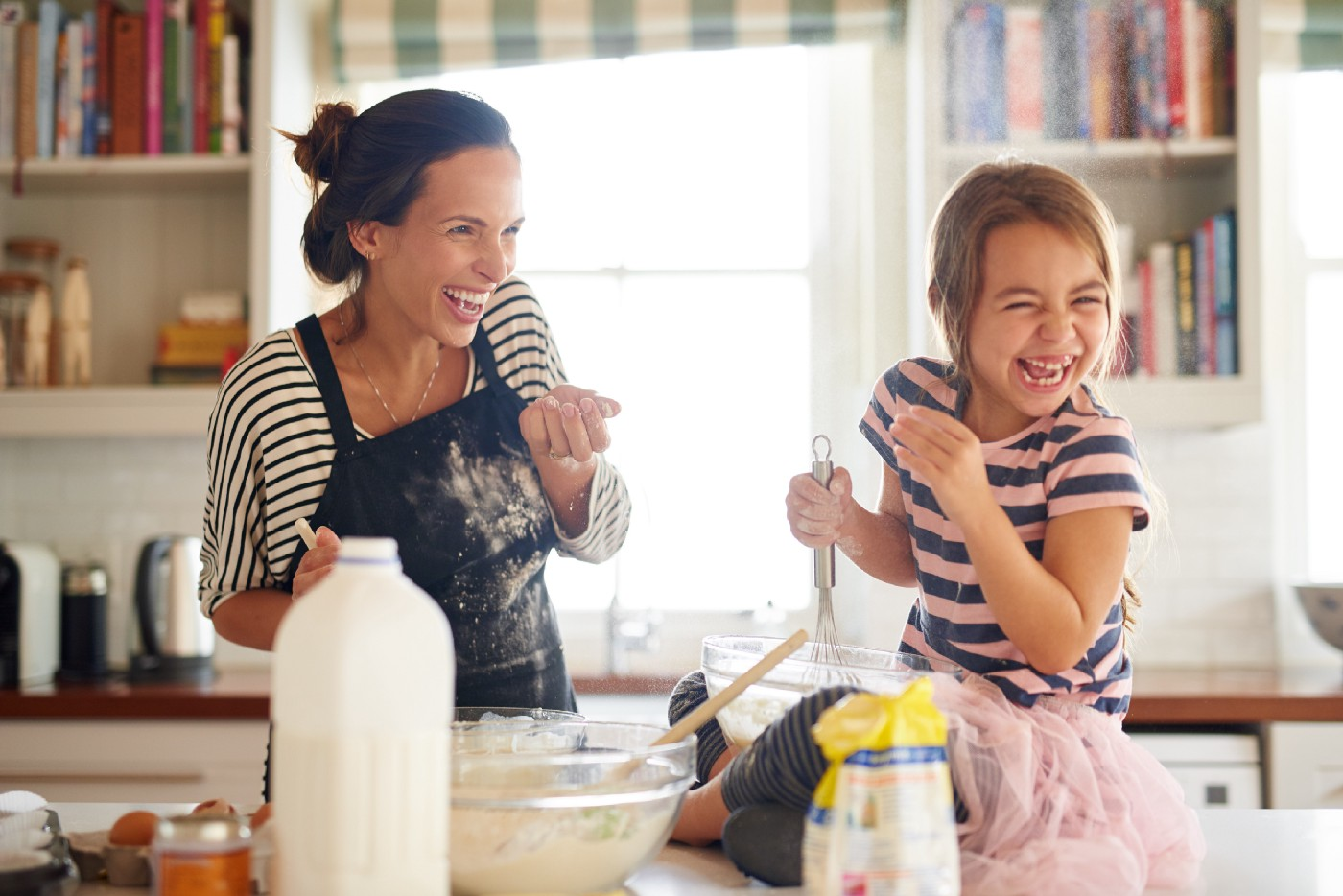 Shot of a little girl having fun baking with her mother in the kitchen