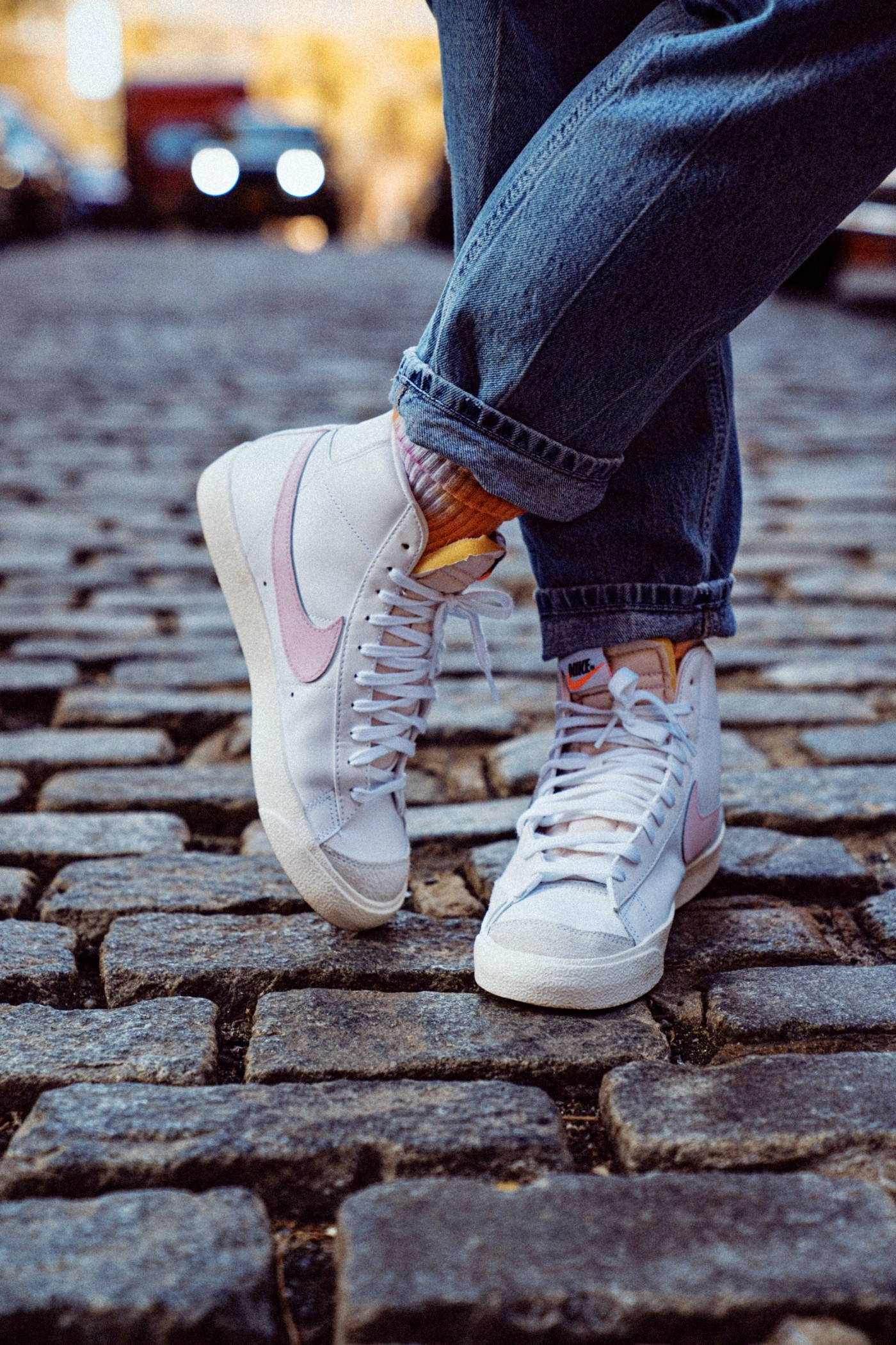 Person wearing white Nikes with a pink swoosh on them.