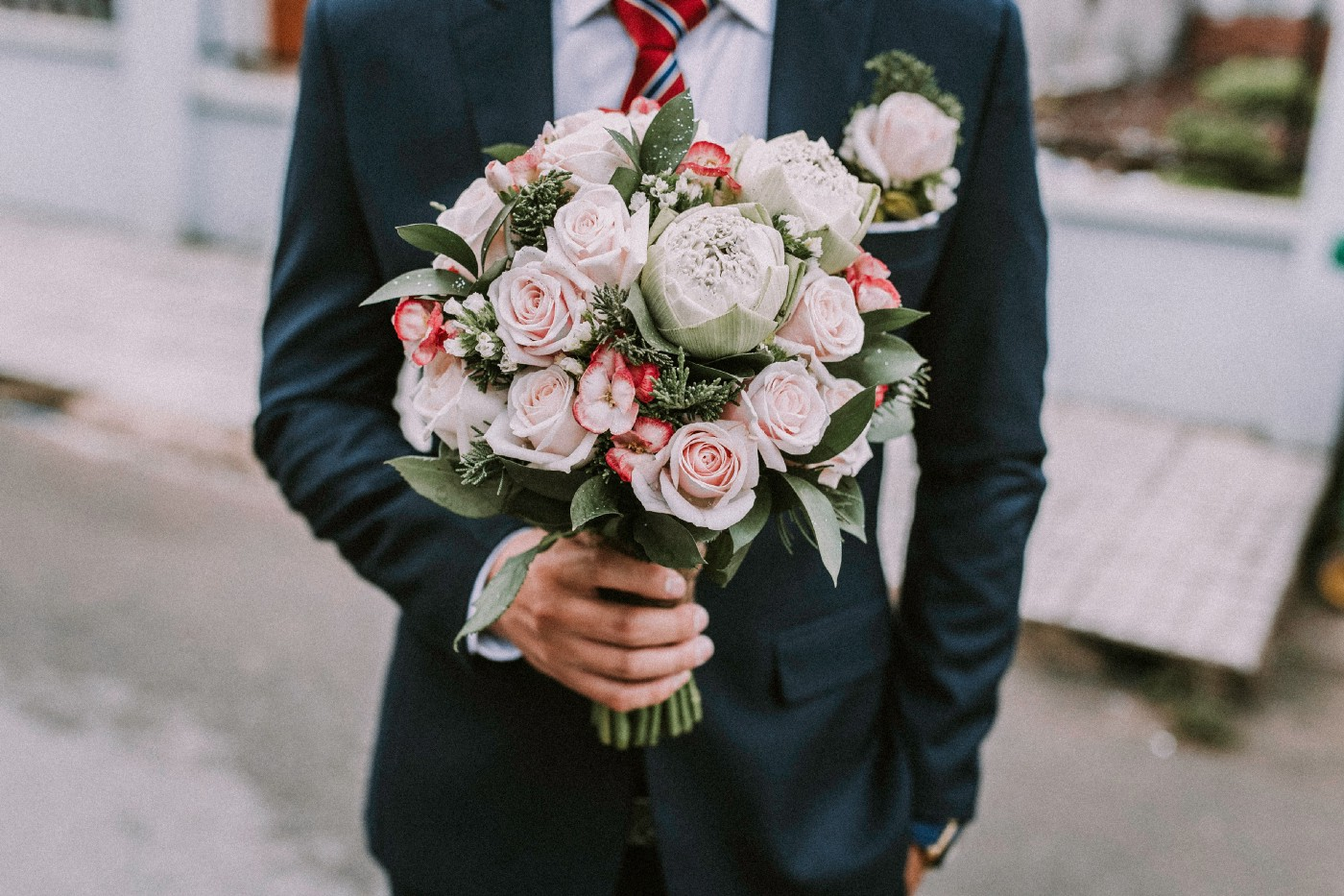 Photo of the torso of a man in a suit holding a bouquet of flowers.