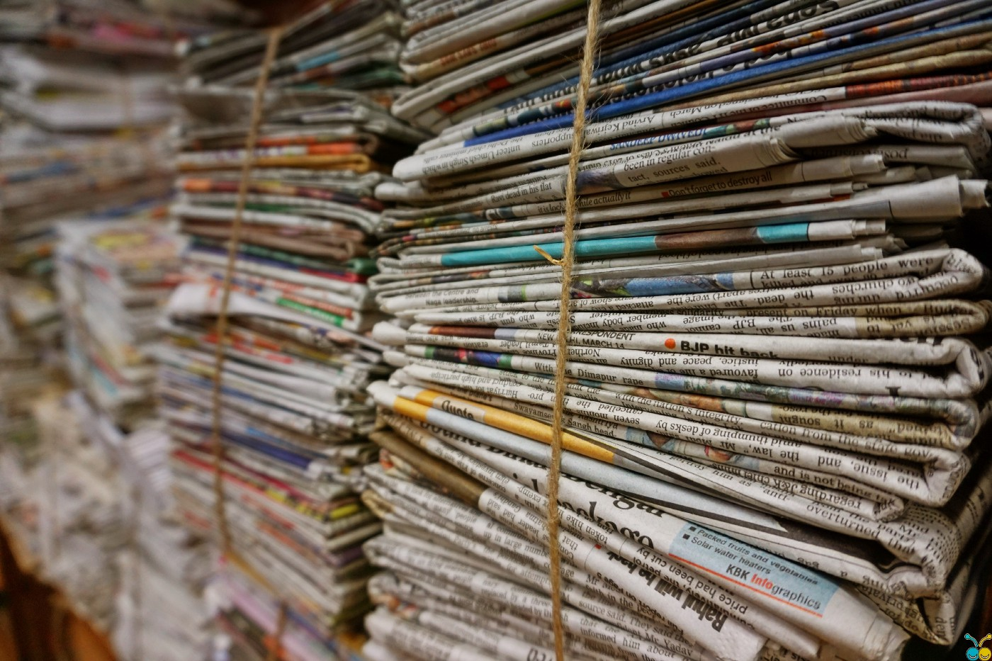 stacks of newspapers folded and bound with twine