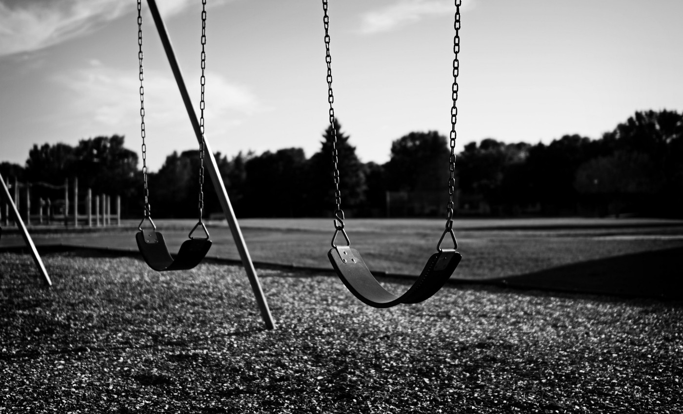 Deserted Playground with two empty swings in black and white