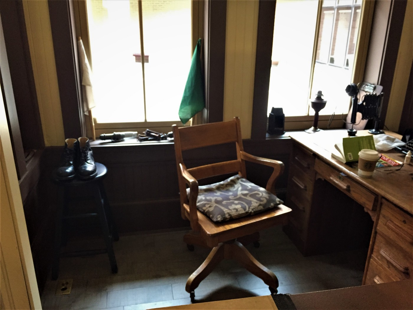 Working replica office of a railway ticket master. Antique items such as boots, chair, desk, party-line phone and lamp in the top right corner. Note: Starbucks cup on desk probably not authentic to the turn of the century time period
