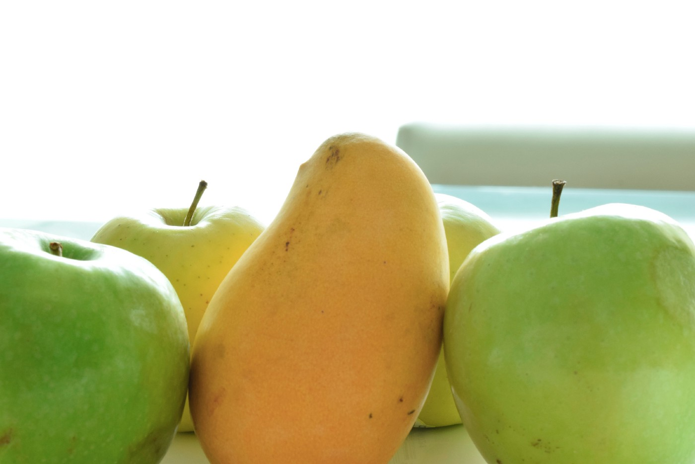 A mango stands tall amongst a group of green apples.