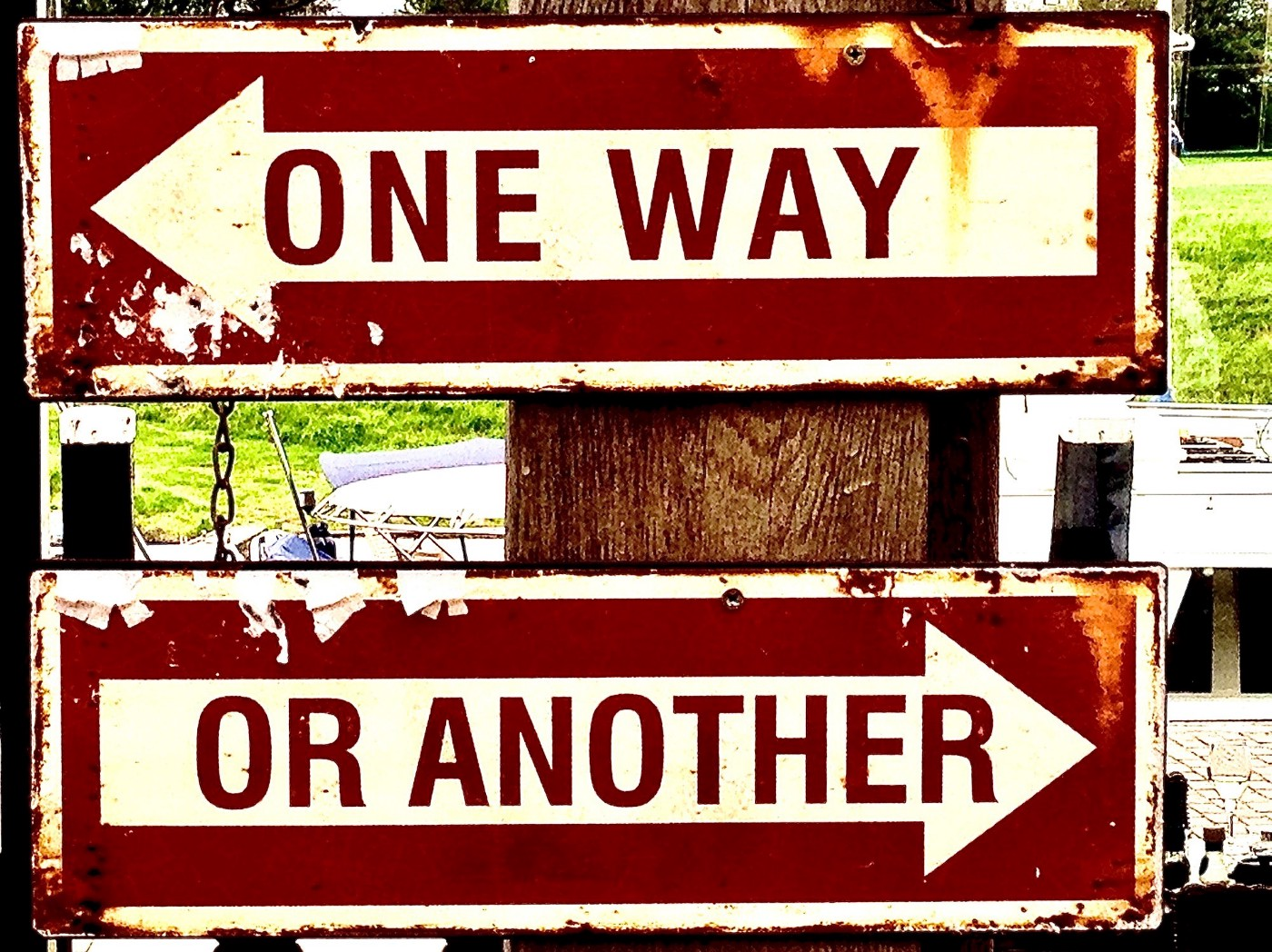 Two red signs. One points left and says 'one way,' the other points right and says 'or another.'