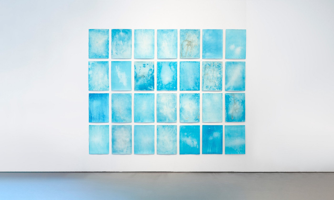 28 abstract paintings with different hues of blue, arranged in 4 raws of 7.