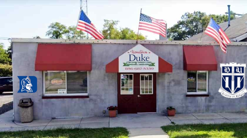 The facade of Hometown Deli with 'Hometown' replaced with the Duke University wordmark, and the Duke shield and Devils logo on its facade.
