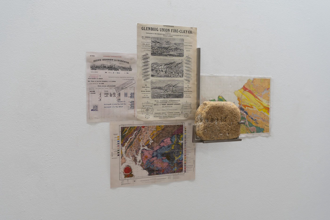 Four cuttings from magazines, a map and a rock hanging on a wall.