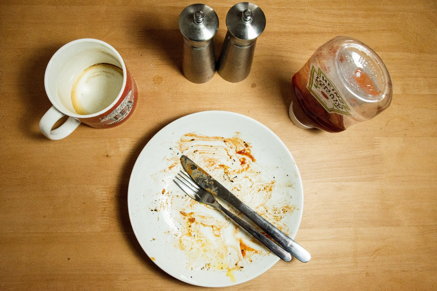 dirty plate and empty cup on table top