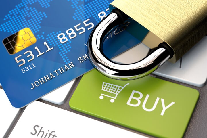 Credit card and padlock on laptop keyboard with buy button and shopping cart icon