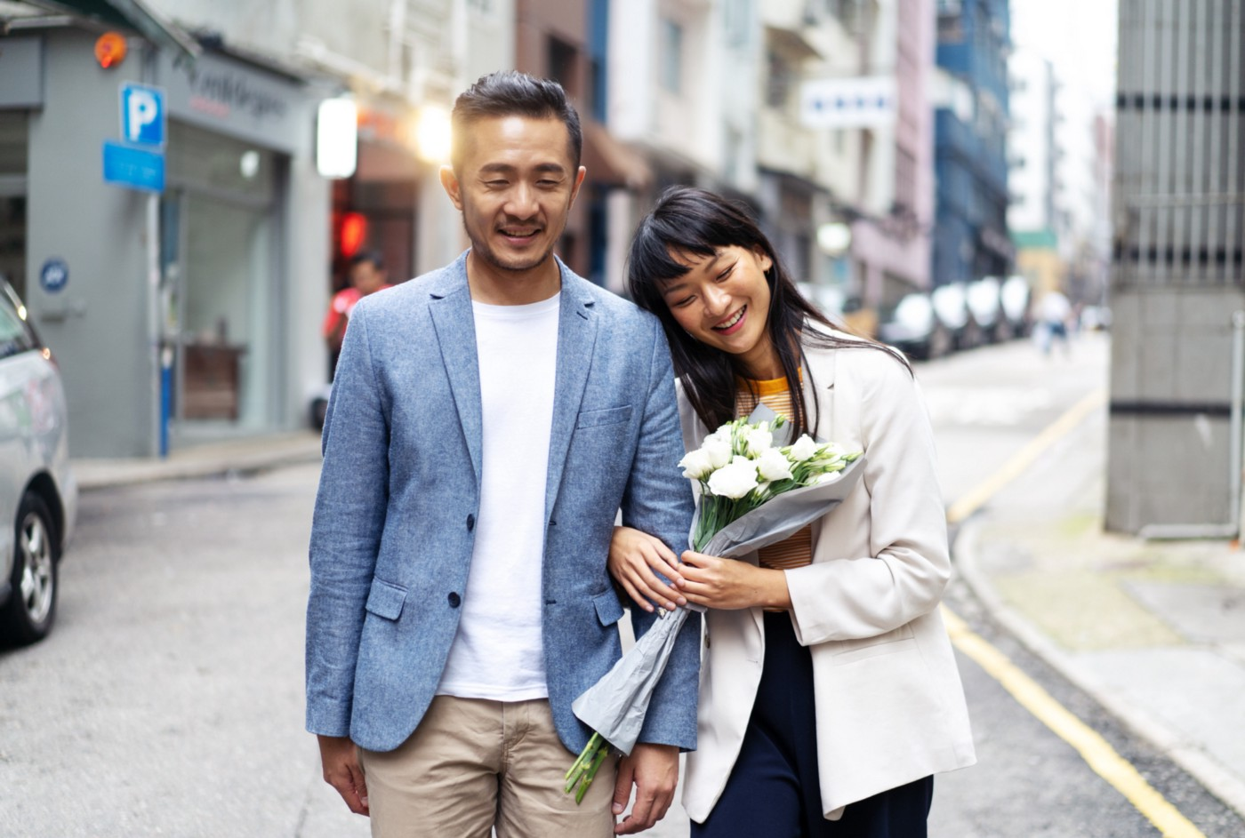 A photo of a happy Asian couple walking down the street. The woman is holding a bouquet of white flowers.
