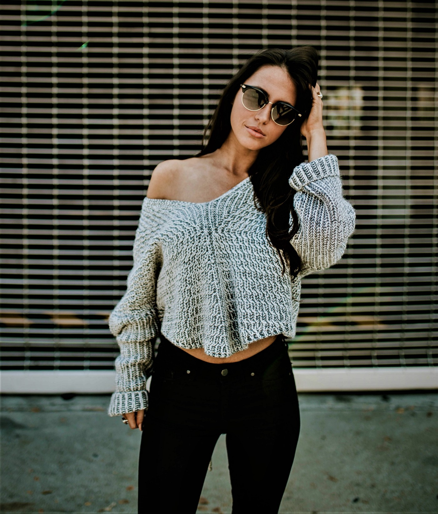 girl with long dark hair wearing sunglasses and long-sleeve off-the-shoulder tan sweater