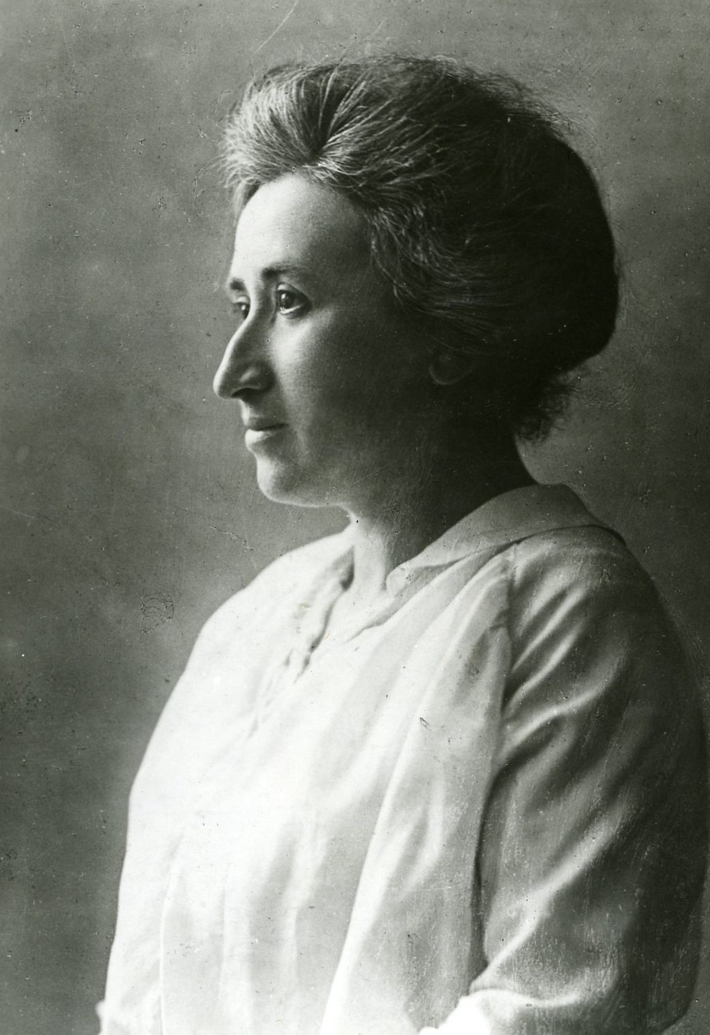 A black-and-white image of Rosa Luxemburg looking toward the left edge of the frame.