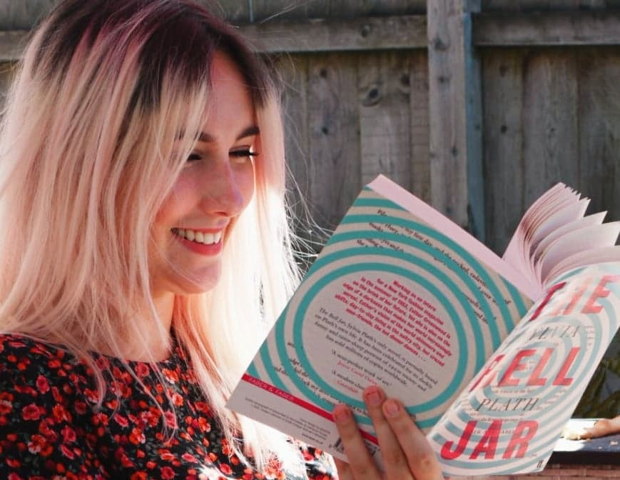 Photo of myself, sat outside in the sunshine reading a copy of The Bell Jar with a swirling aqua and pink cover.