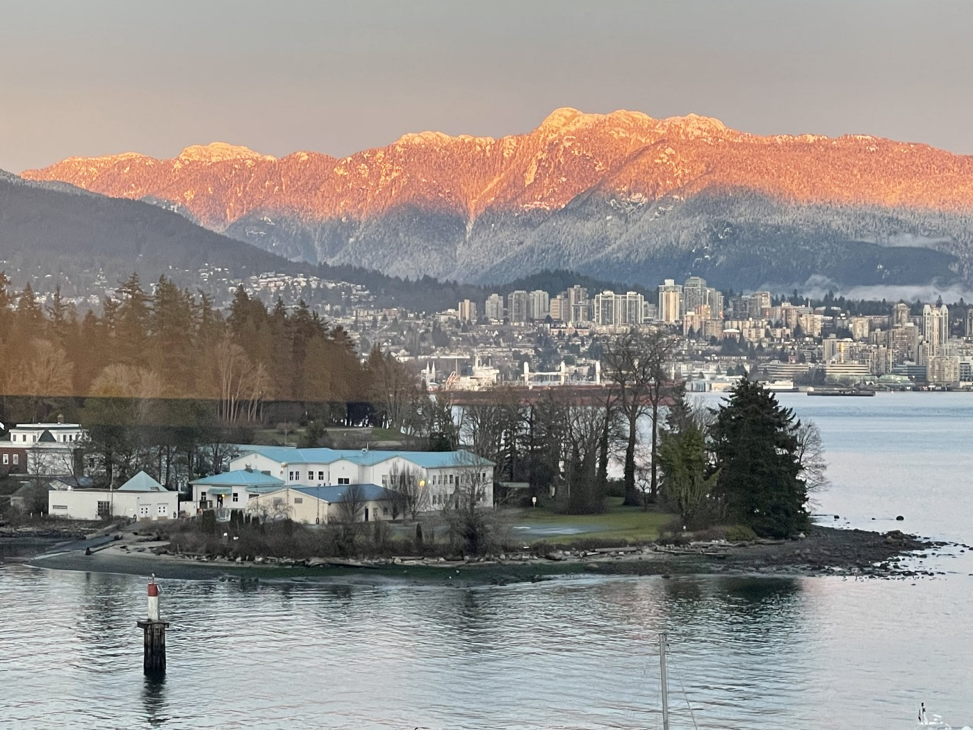 Rosy late light illuminating snow covered mountains behind sky scrappers. A harbour island with evergreen  forest, mists