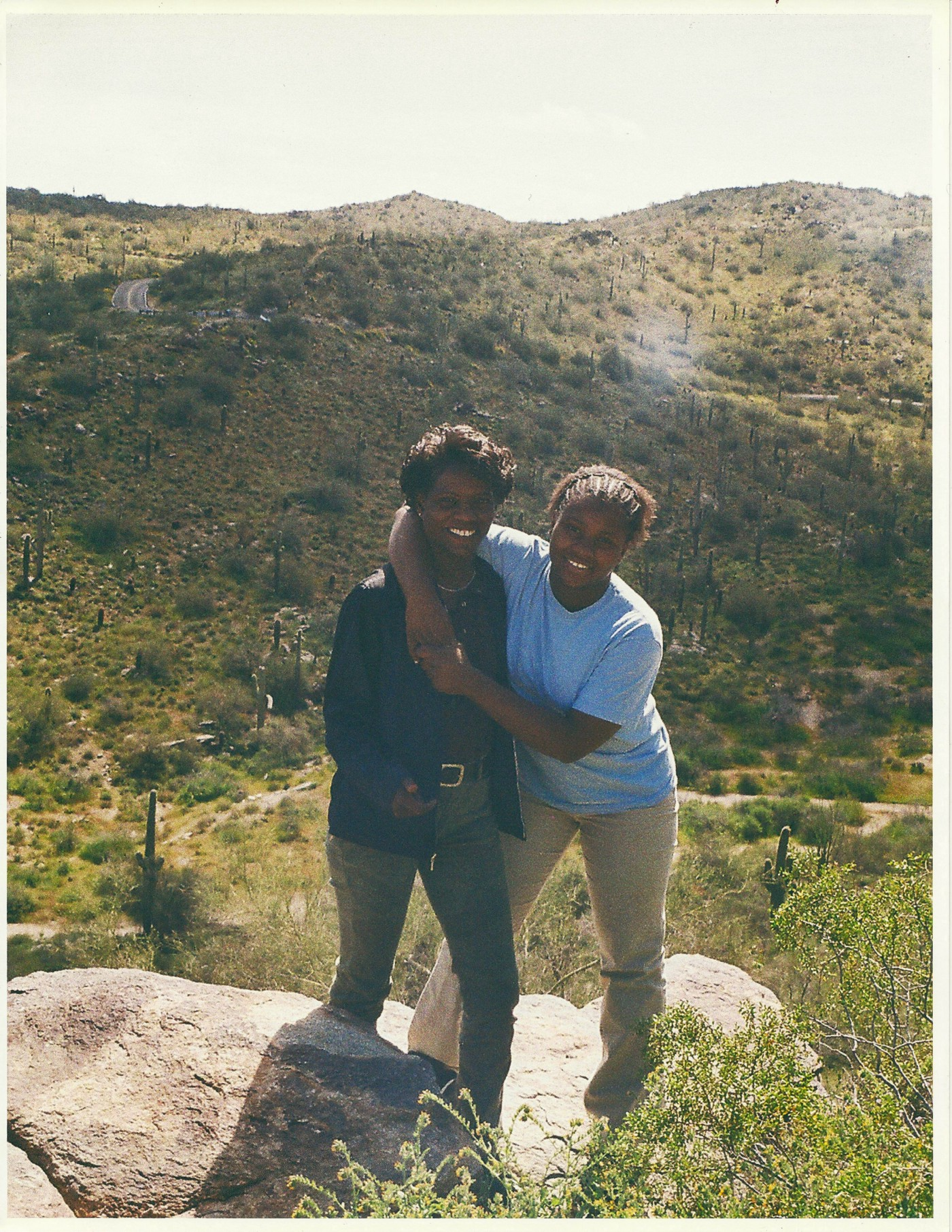 Nicole and her mom hiking near the Prescott National Forest in Arizona. Nicole has her arms around her mom and both are smiling with hills and trees in the background. Photo credit: Nicole Hams