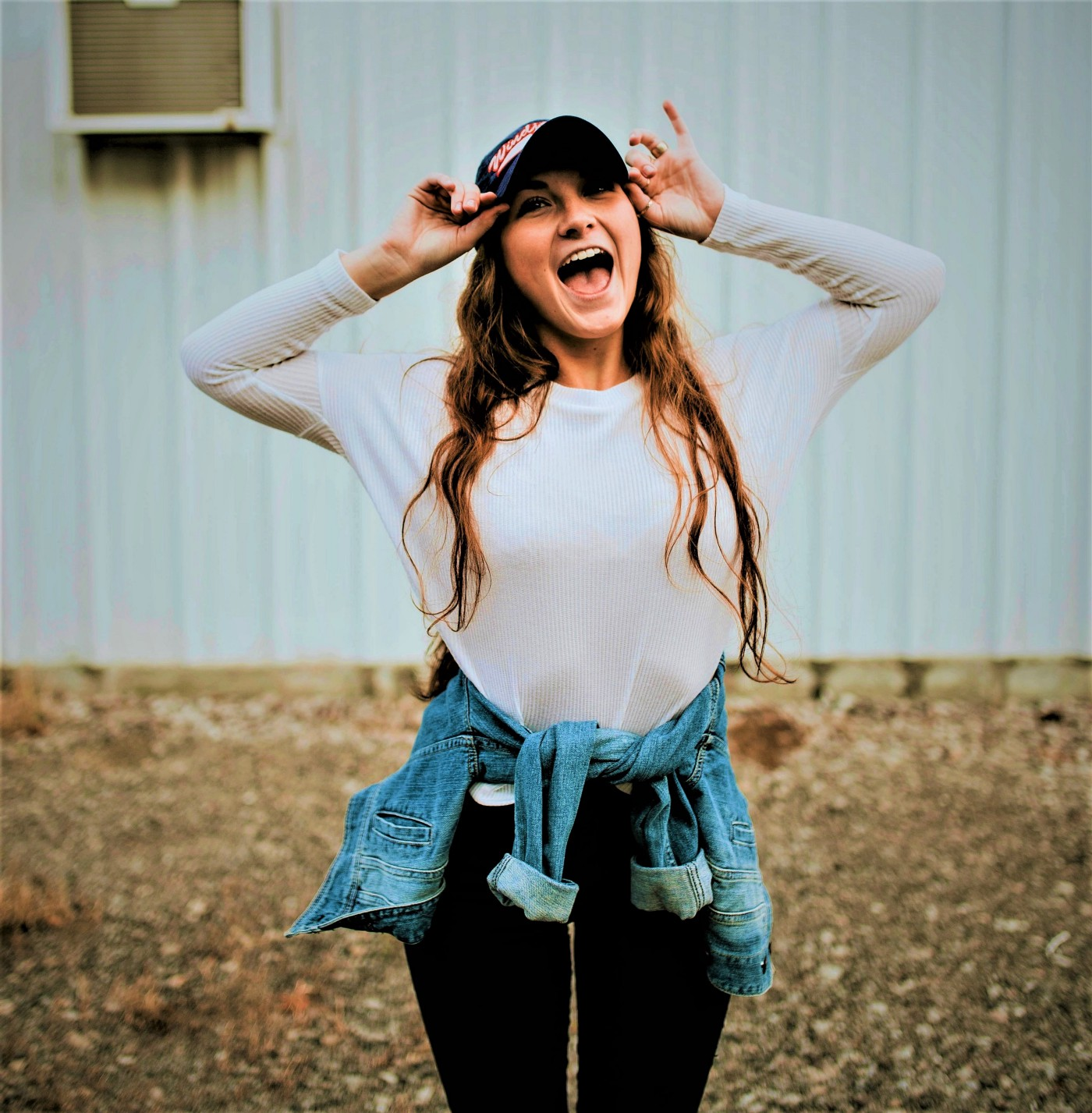 happy girl with long brown hair wearing long sleeve light top and baseball cap