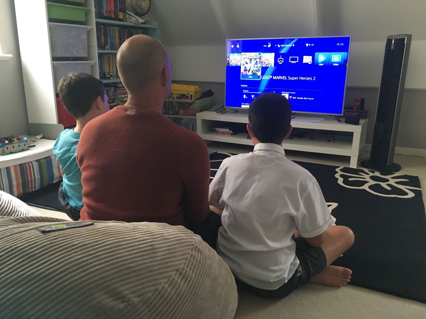 Dad and boys enjoy a PlayStation game