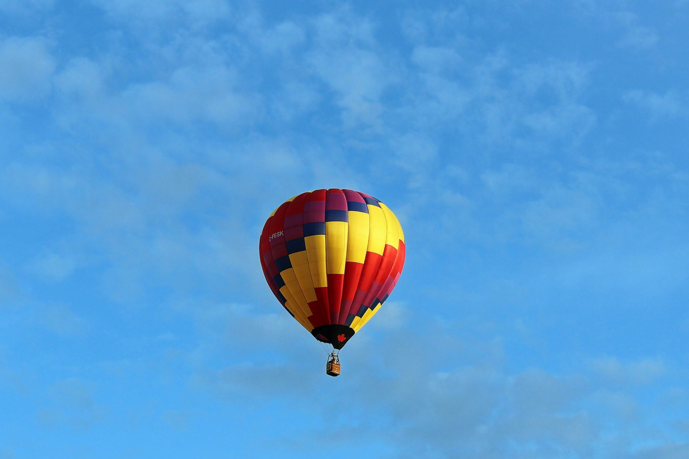 Multicolored hot air balloon in blue sky.