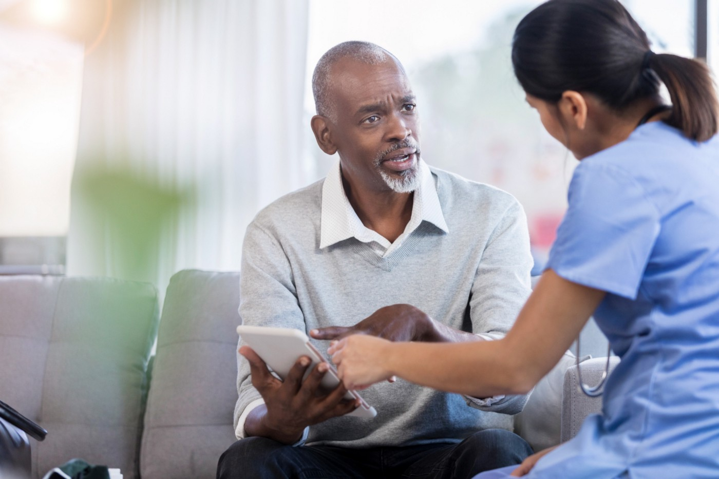 A man asks his doctor a question while pointing at his diagnosis on the tablet.