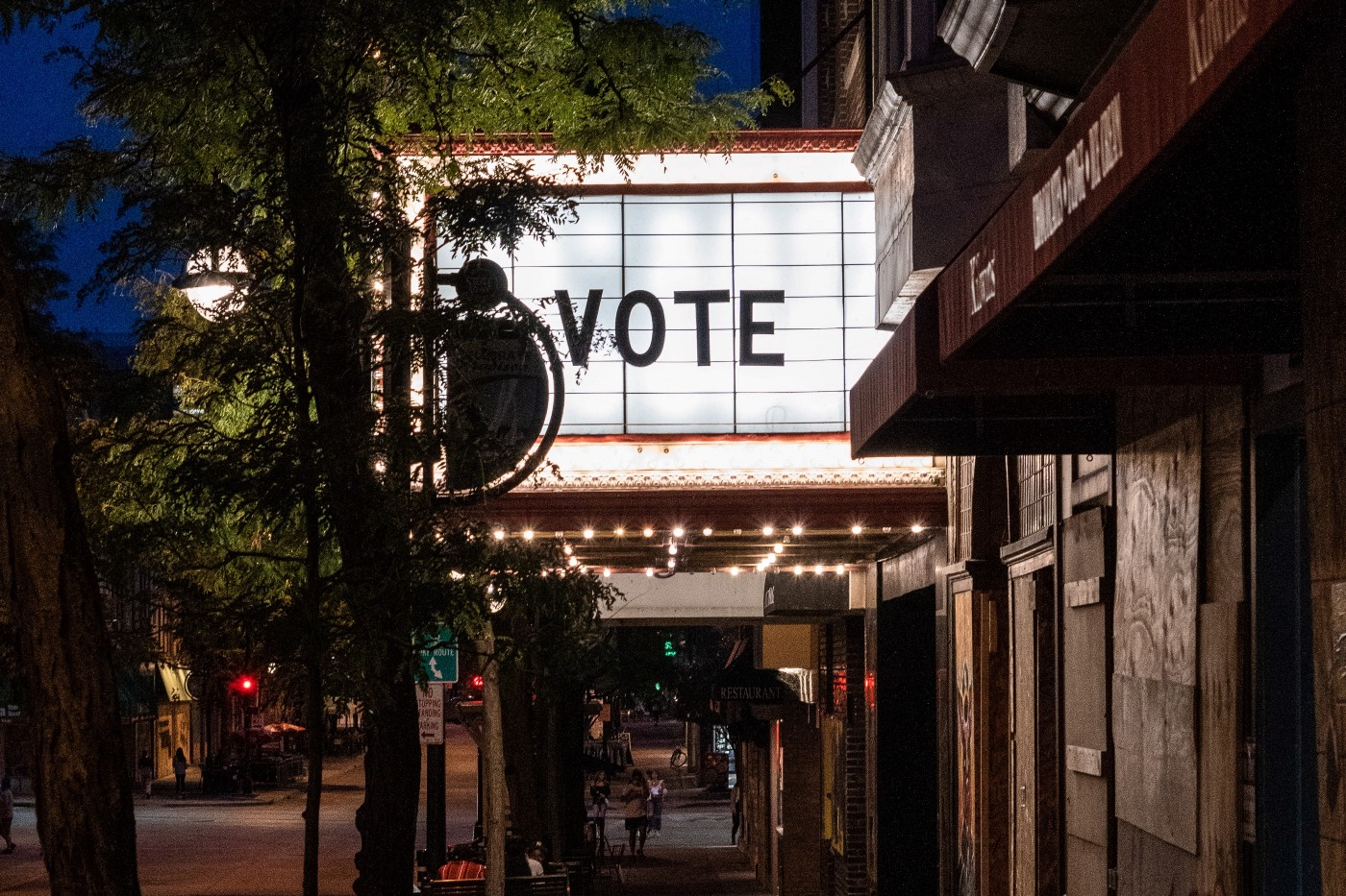 "Movie theatre marquee with the word ""VOTE"" and a tree, at night"