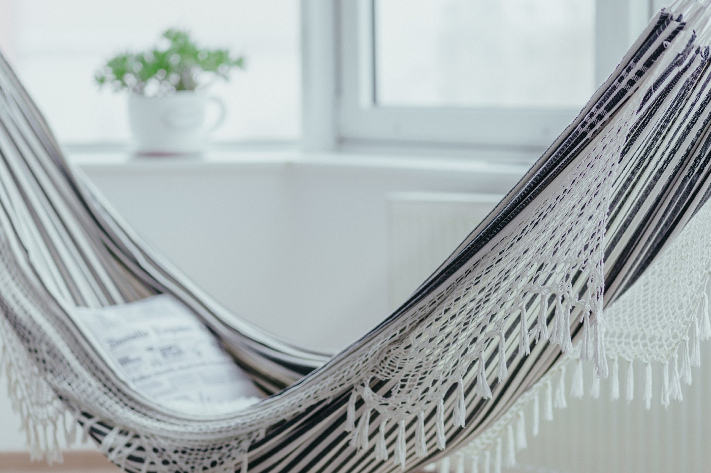 A grey and white fringed hammock with pillow inside a light-filled room with windows, a plant in a white vase.