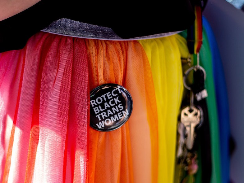 """Close up of the rainbow skirt of a Gay Pride participant. A pin on the skirt reads """"Protect Black Trans Women."""""""