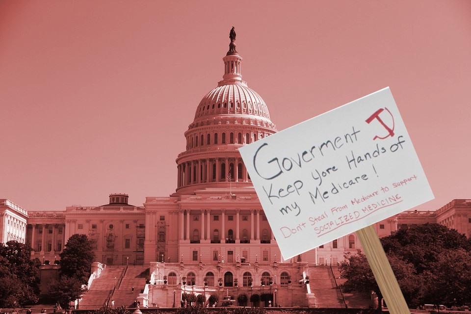 A red-tinted image of the capital dome. In the foreground, a hand-lettered protest sign bearing a crude hammer and sickle, reading 'Government keep yore (sic) hands of (sic) my Medicare! Don't steal from Medicare to support SOCIALIZED MEDICINE.'
