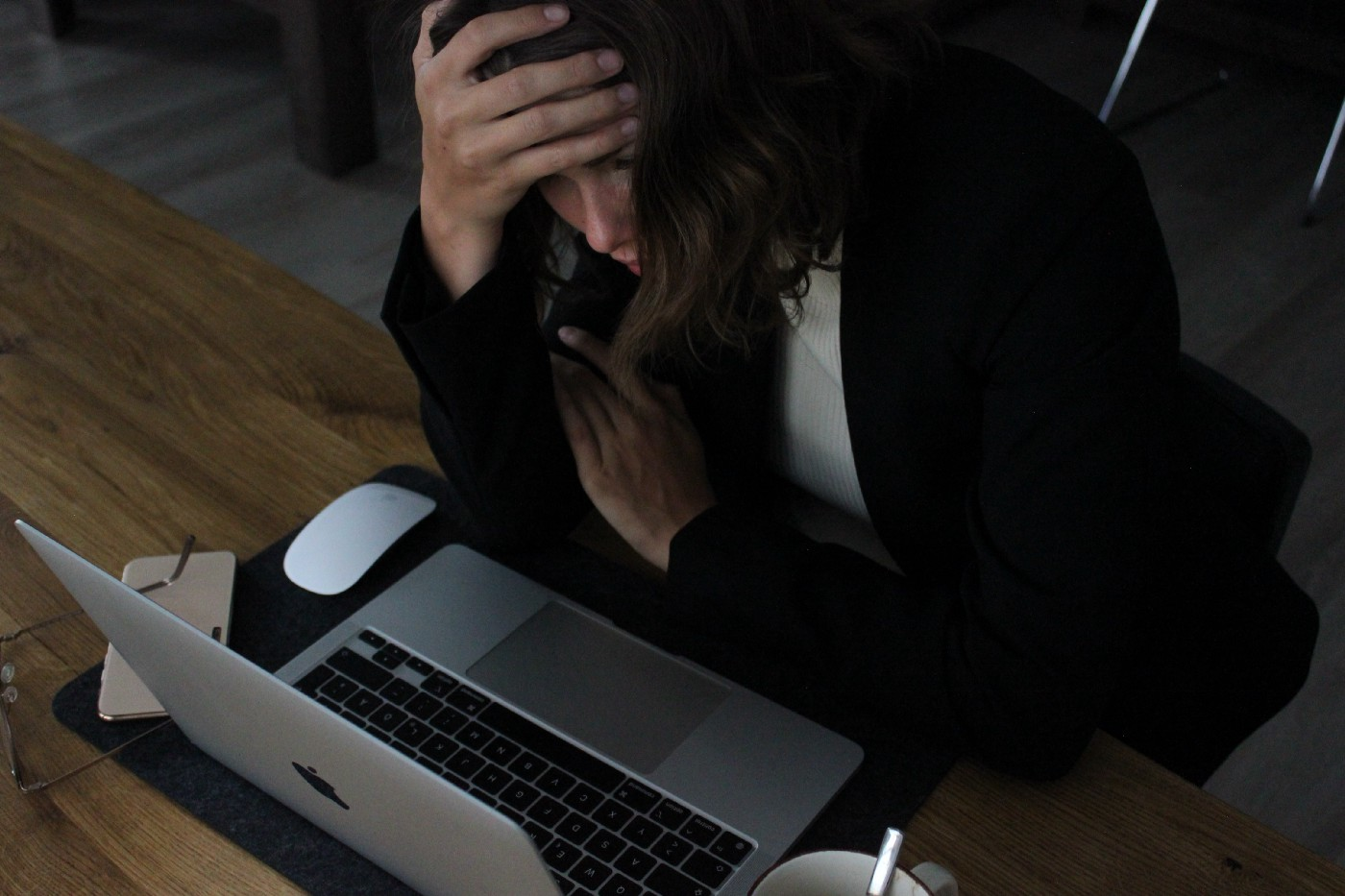 Woman leaning over laptop with her head in her hand, looking sad and tired.