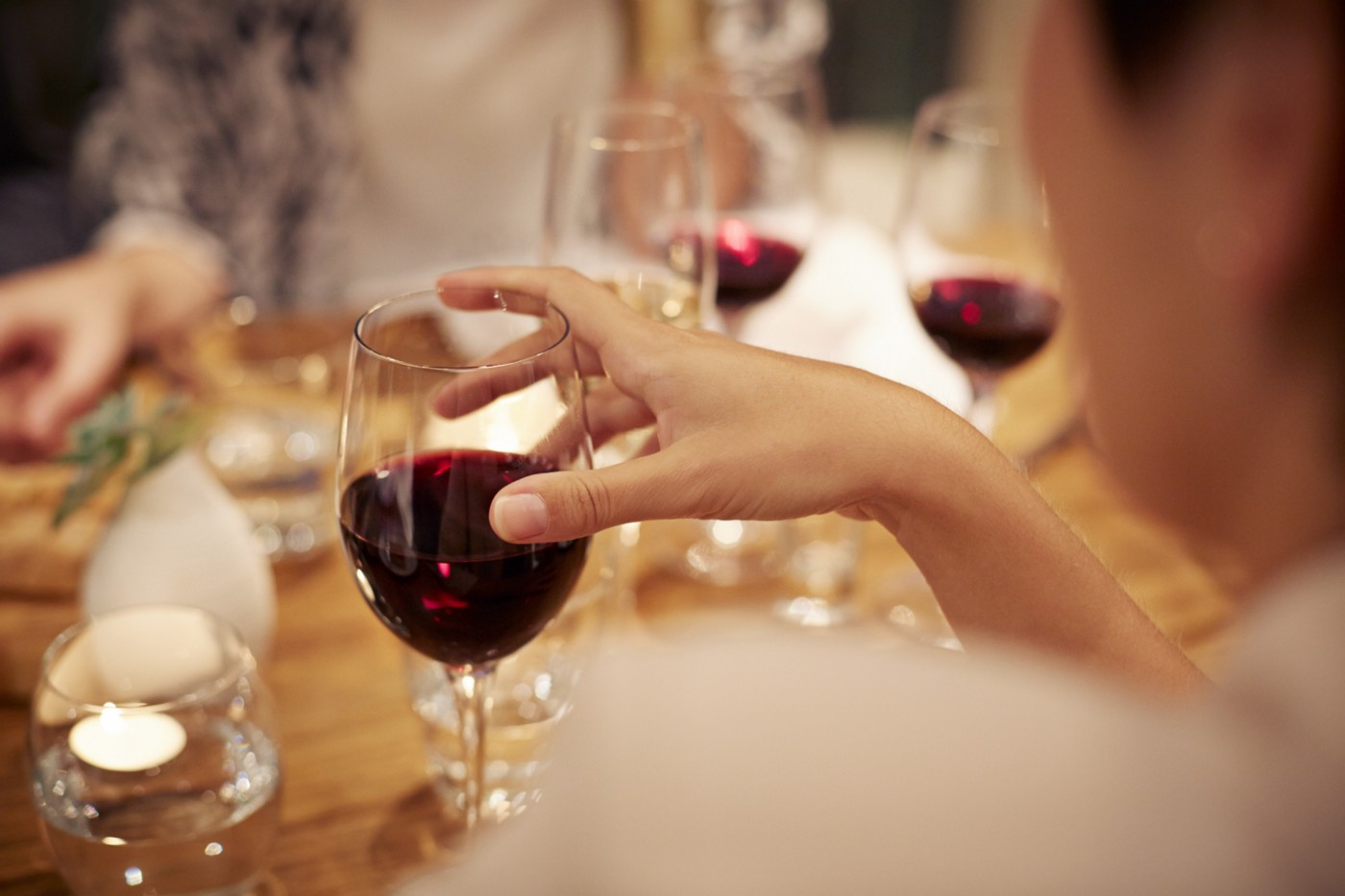 Woman holding a wine glass filled with red wine.