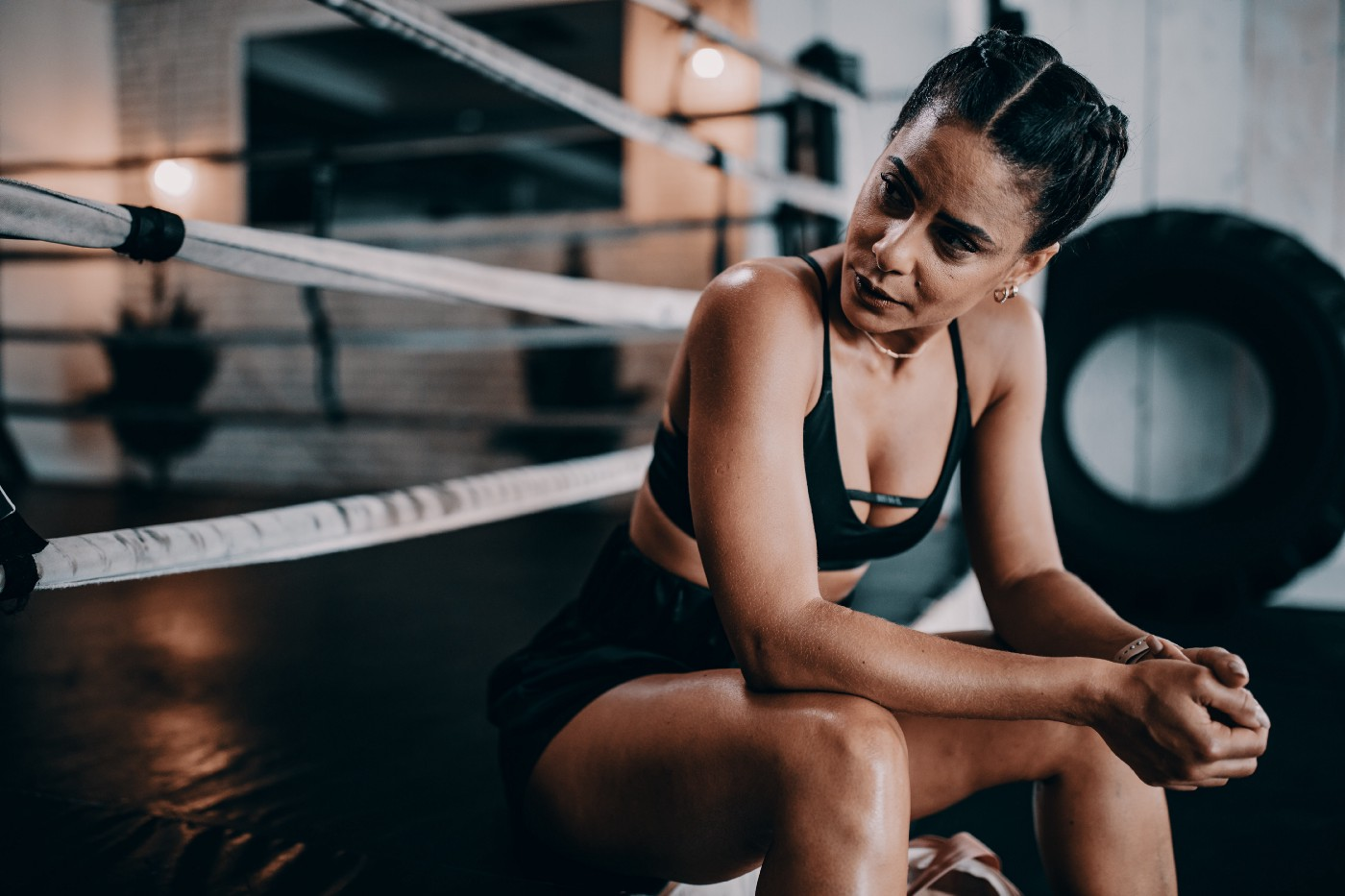 """Ethnically ambiguous womxn in black activewear sits on the side of a boxing ring. Her face says """"try me."""""""