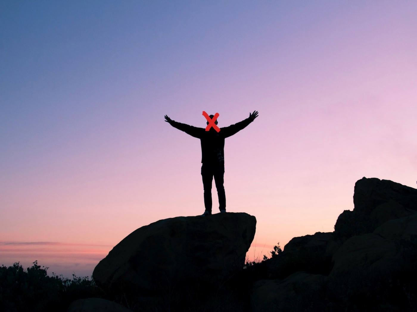 A generic stock photo of a man on a rock with his arms outstretched.