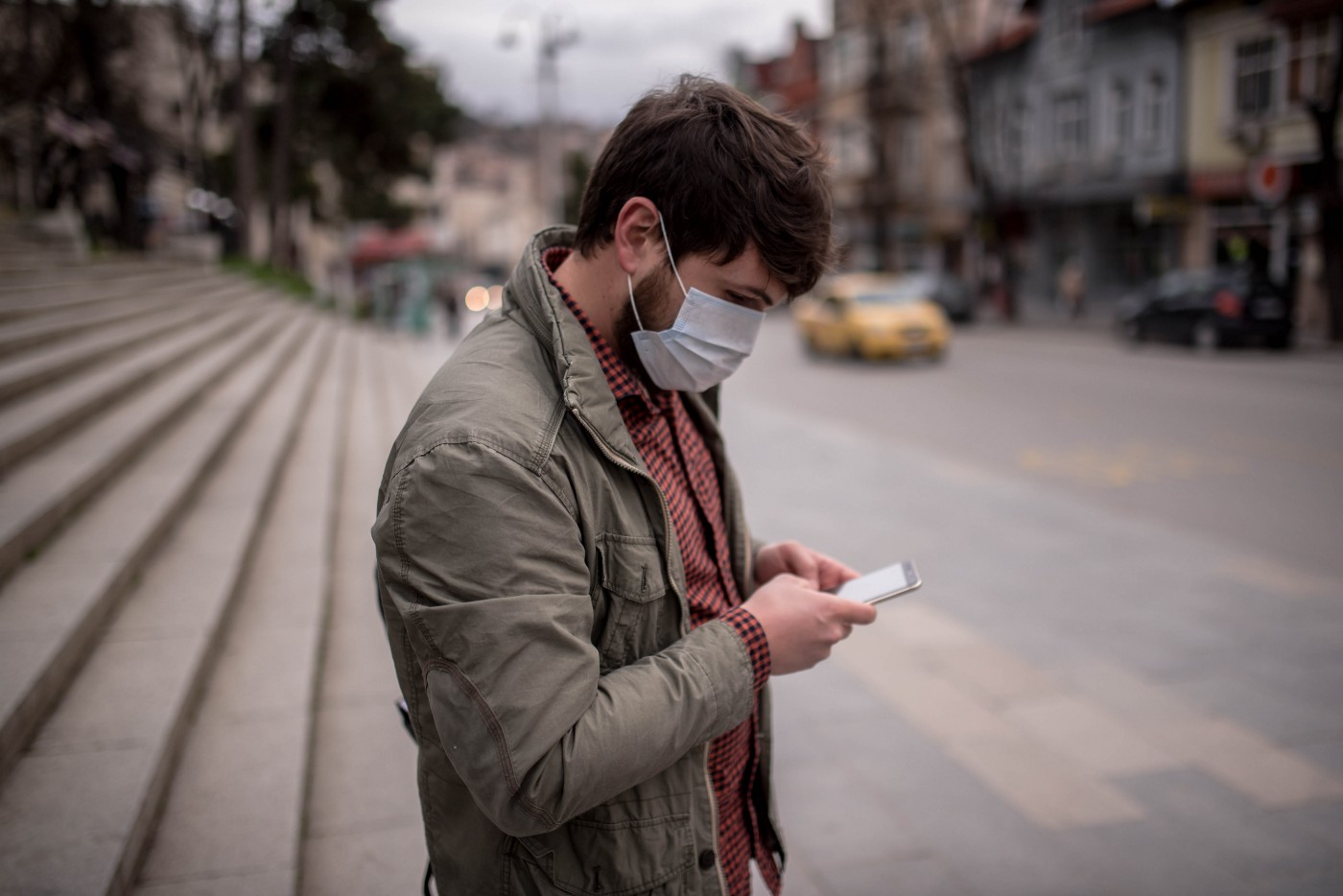 A man wearing a face mask types into his phone.