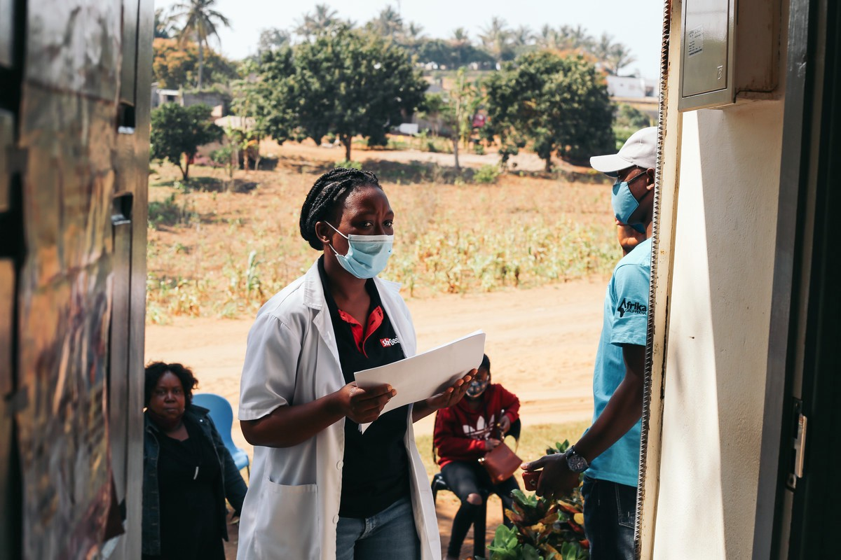 A masked healthcare worker is going door-to-door to deliver healthcare services in Mozambique.
