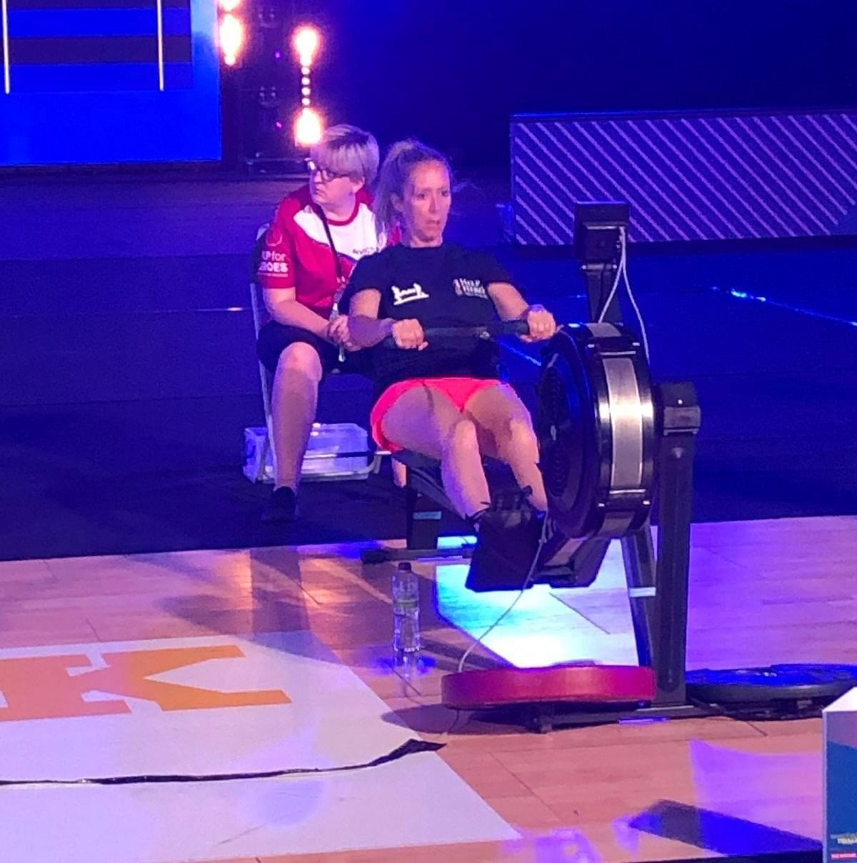 A woman competes on a rowing machine in a large hall