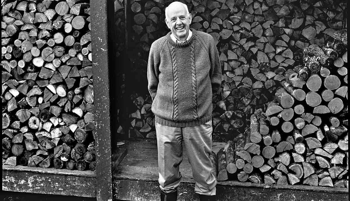 Farmer-philosopher Wendell Berry standing by a pile of chopped wood.