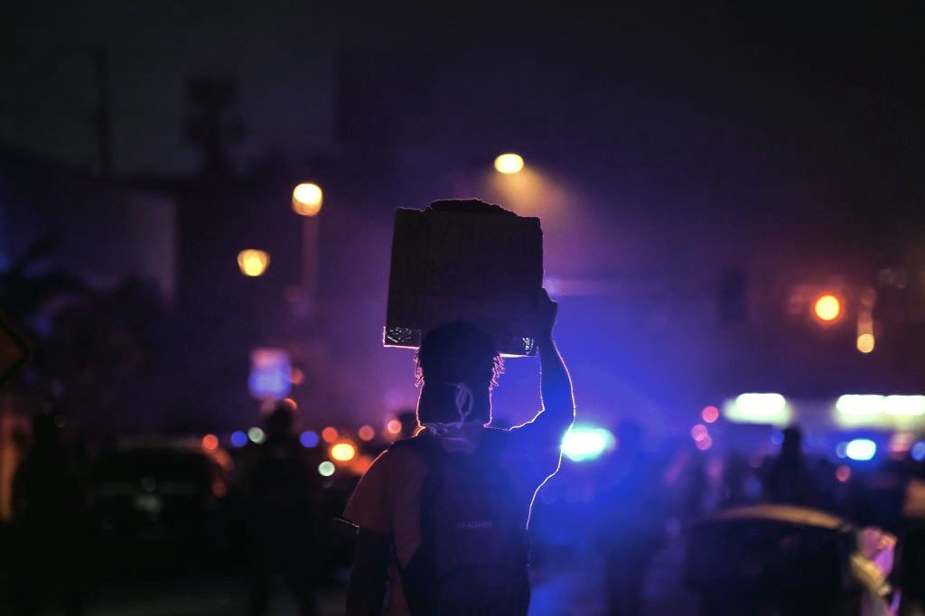 A dark nighttime photo of a protestor holding up a sign with police lights in the background.