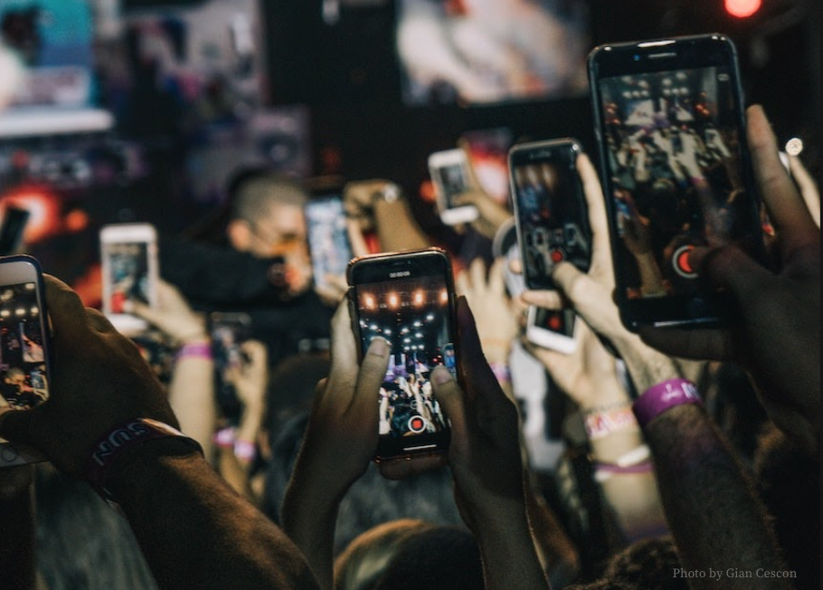 A crowd of people at a concert holding up their phones to film the concert