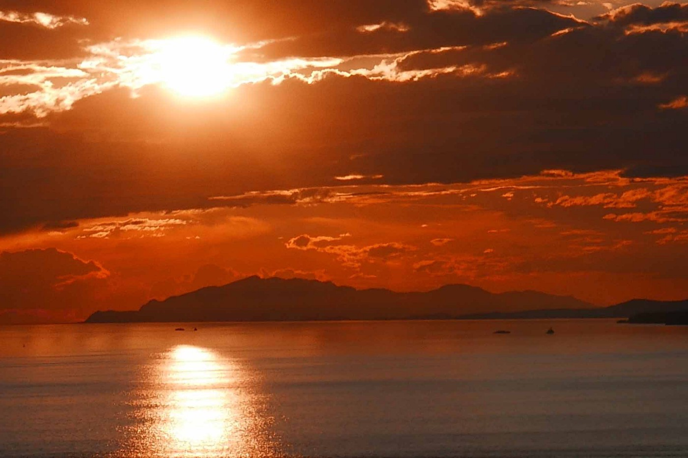 The sun spills through tattered layers of crimson clouds reflecting on calm water punctuated by a few small boats. Islands demarcate sky and sea