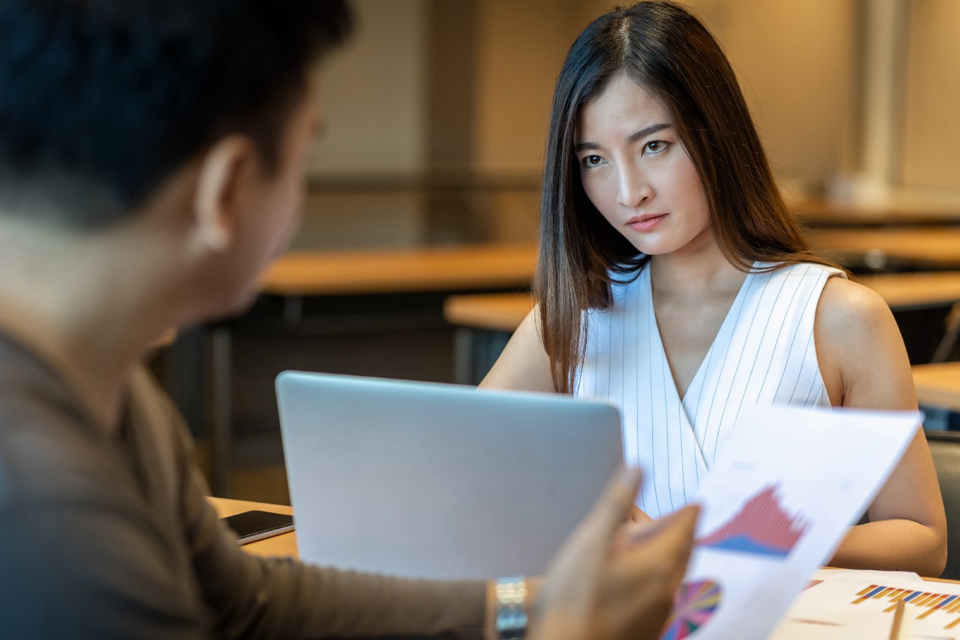 A young woman glares as her boss scolds her for making a mistake on a business report.