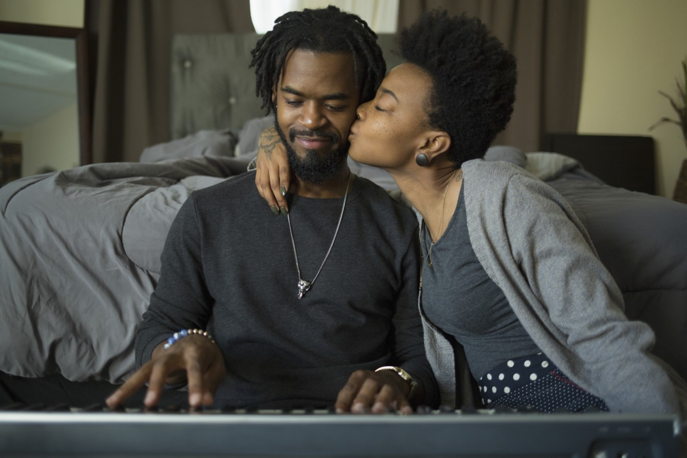 A photo of a black couple. He is playing keyboard and she kisses him on the cheek.