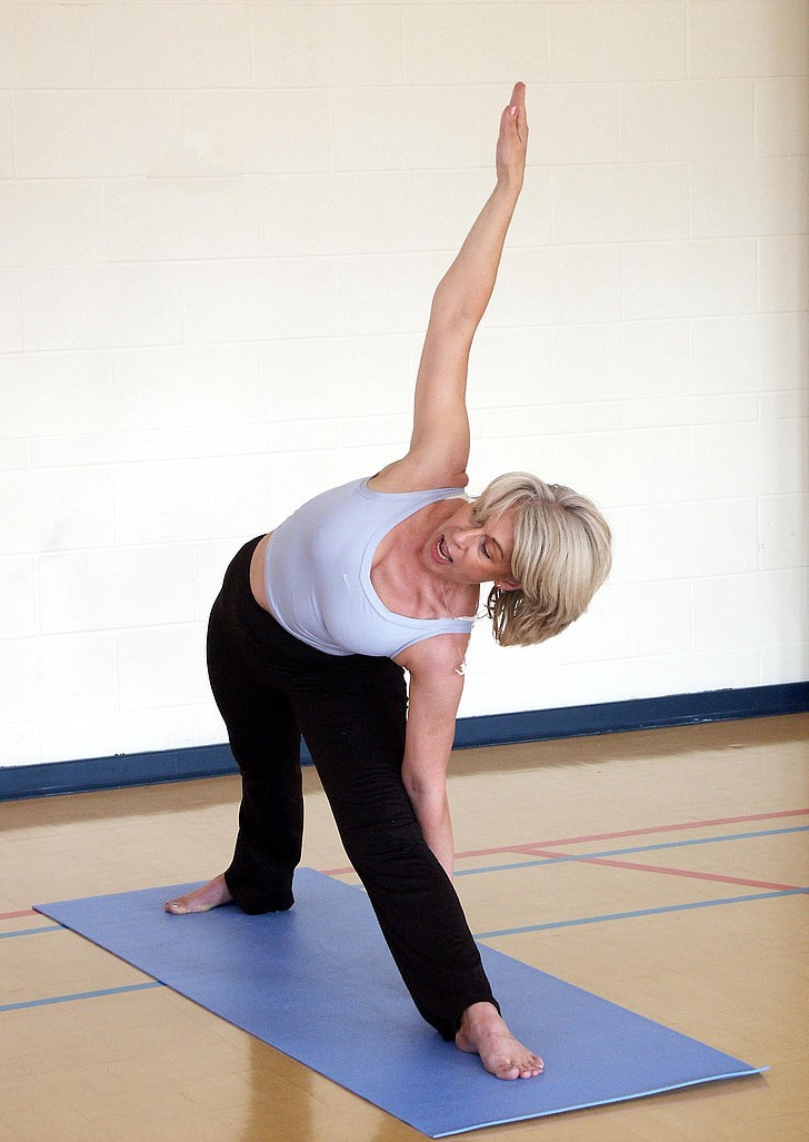 A woman wearing black trouser and white inner wear practicing yoga.