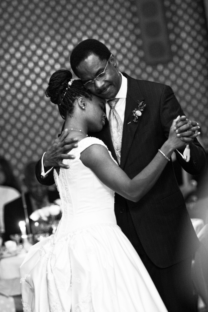 A black bride and her father hug while dancing.