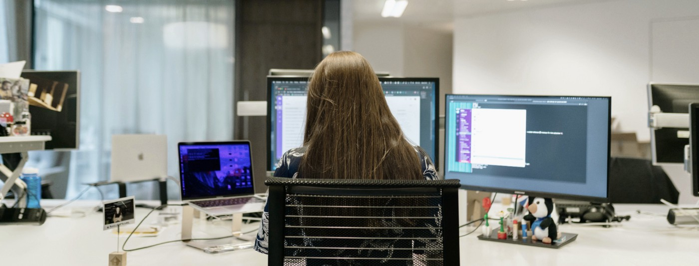 Back of a software engineer's head as she reviews code on triple monitors in an office setting