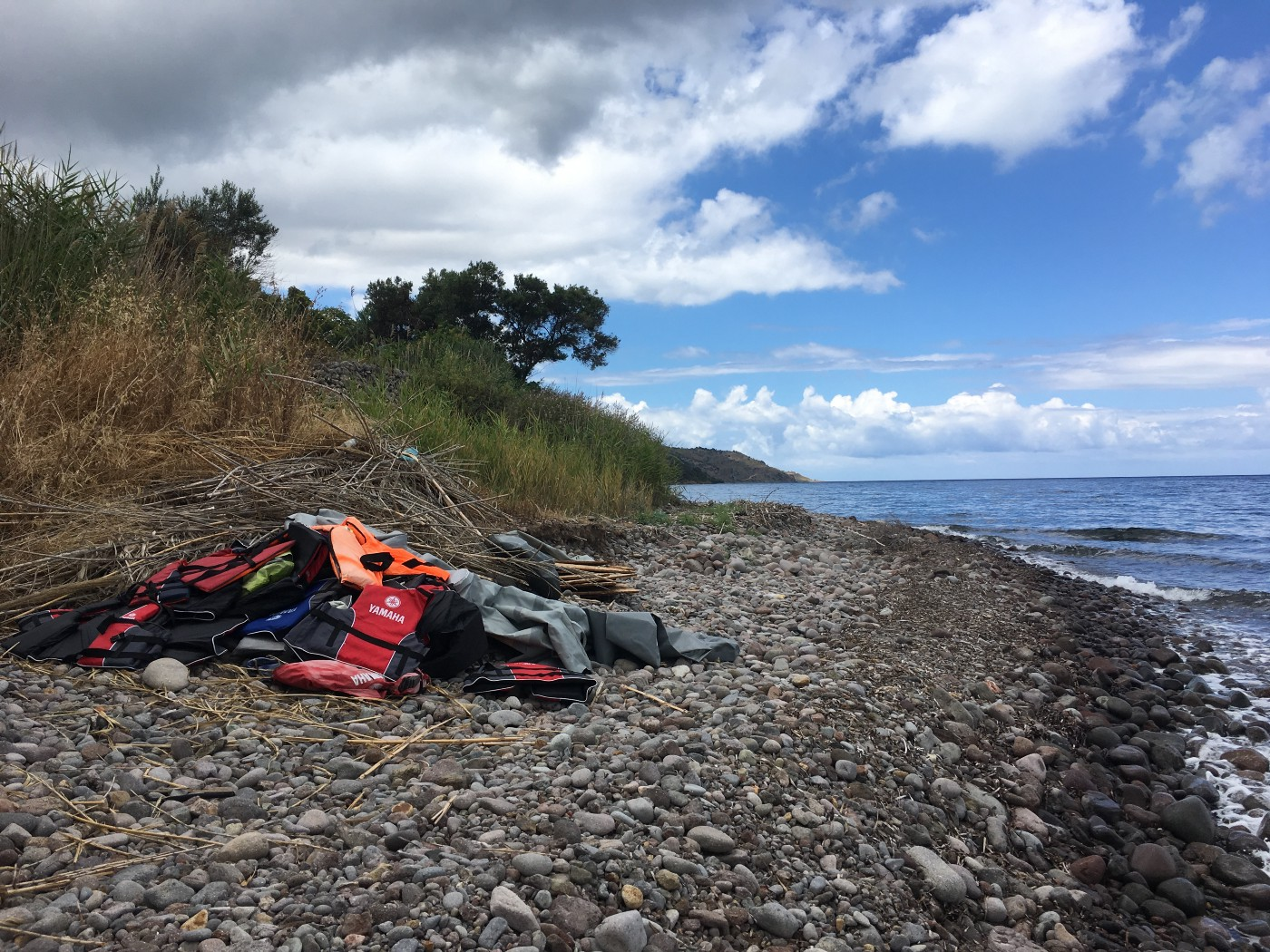 A pile of life jackets on the rocky shore of Lesbos.