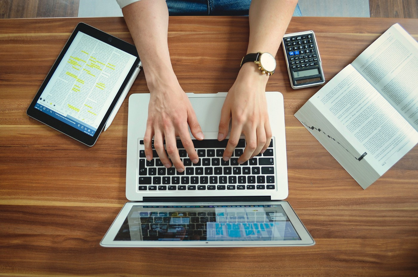 Two hands on a laptop keyboard. There is a calculator, an open book and a tablet on the table.
